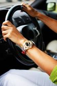 Woman hands on a steering wheel — Stock Photo