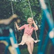 Woman sitting on a swings — Foto Stock