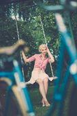 Woman sitting on a swings — Stock Photo