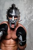 Man in boxing gloves and gladiator helmet — Stock Photo