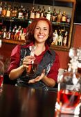 Barmaid with bottle behind bar counter — Stock Photo