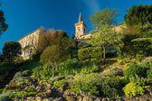 Klocktornet och hus på en trädgård kulle — Stockfoto