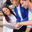 Group of friends with laptop sitting on a steps outdoors — Stock Photo #32303659