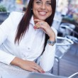 Smiling young brunette woman alone with laptop in summer cafe — Stock Photo