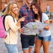Three friends tourist with map outdoors — Stock Photo