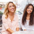 Two beautiful girls chatting in summer cafe — Stock Photo