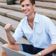 Handsome young man with laptop sitting on a steps outdoors — 图库照片