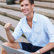 Handsome young man with laptop sitting on a steps outdoors — Stock Photo
