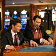 Two young cheerful men behind table in a casino — Stock Photo