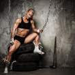 Beautiful muscular bodybuilder woman sitting on tyres and holding chains — Stock Photo