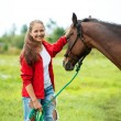 Beautiful smiling girl with her brown horse outdoors — Stock Photo