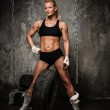 Beautiful muscular bodybuilder woman posing against tyres and chains — Stock Photo