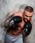Young sporty man in boxing gloves in motion — Stock Photo