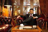 Jistý pohledný bruneta sedí v luxusním interiéru — Stock fotografie