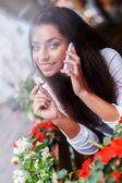 Улыбается молодой женщины с мобильным телефоном среди цветов на летней террасе — Стоковое фото