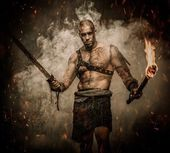 Gladiator standing in a smoke with torch and sword — Stock Photo