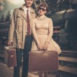 Vintage style couple with suitcases on  train station — Stock Photo