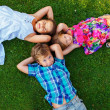 Stock Photo: Happy children lying on a meadow