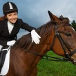Smiling girl sitting on a horse — Stock Photo