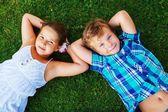 šťastné děti leží na louce — Stock fotografie