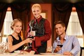 Young couple in restaurant and waitress with bottle of wine — Stock Photo