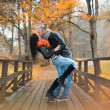 Happy middle-aged couple kissing outdoors on beautiful autumn day — Zdjęcie stockowe