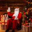 Santa Claus sitting on rocking chair in wooden home interior with gift boxes around him — Stok fotoğraf