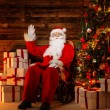 Santa Claus sitting on rocking chair in wooden home interior with gift boxes around him — Foto Stock