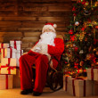 Stock Photo: Santa Claus sitting on rocking chair in wooden home interior with gift boxes around him