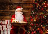 Santa claus in houten interieur zitten achter de tabel en het schrijven van brieven met ganzenveer — Stockfoto