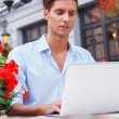 Young man with laptop — Stock Photo