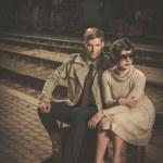 Beautiful vintage style couple sitting on suitcases on train station platform — Stock Photo