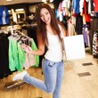 Beautiful happy brunette girl with shopping bag in a sport outlet — Stock Photo