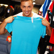 Handsome young man choosing t-shirt in a sport outlet — Stock fotografie