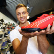 Young handsome man choosing sport footwear in sport outlet — Stock Photo #33867479