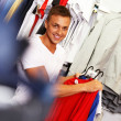 Handsome young man choosing t-shirt in a sport outlet — Stok fotoğraf
