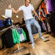 Handsome young man with shopping bag jumping in sport outlet — Foto Stock