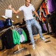 Handsome young man with shopping bag jumping in sport outlet — Stock Photo