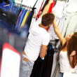 Happy young couple with shopping bag in choosing sportswear in store — ストック写真