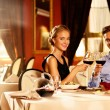 Beautiful young couple with glasses of red wine in luxury restaurant — Stock Photo #33868091