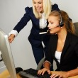 Beautiful help desk office support woman with female boss behind her — Stock Photo