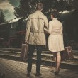 Beautiful vintage style couple with suitcases on  train station platform — Stock Photo