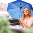 Girl with blue umbrella sitting in summer cafe — Stock Photo