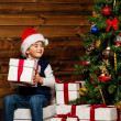 LIttle boy opening gift box under christmas tree — ストック写真