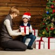 Mother and her boy in Santa hat with gift box under christmas tree — Stock Photo #33868445