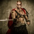 Stock Photo: Wounded gladiator with sword covered in blood