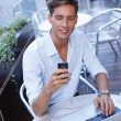 Handsome young man with laptop and mobile phone in a summer cafe — Stockfoto