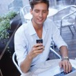 Handsome young man with laptop and mobile phone in a summer cafe — Stock fotografie