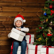 LIttle boy in Santa hat with gift box under christmas tree — Stock Photo