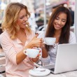 Two beautiful girls cups and laptop in summer cafe — Stock Photo